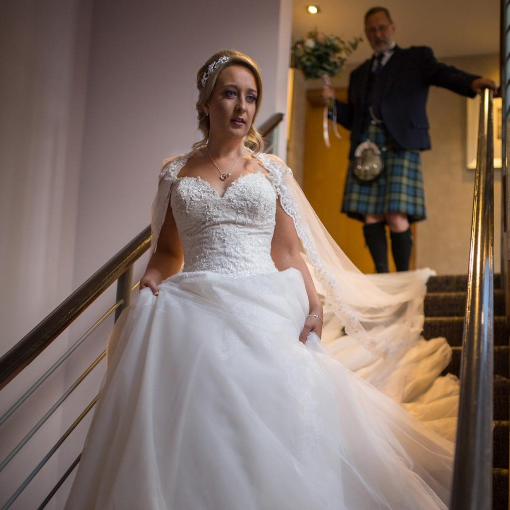 Bride walking down stairs with dad behind her